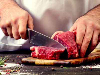 Man cutting red beef meat