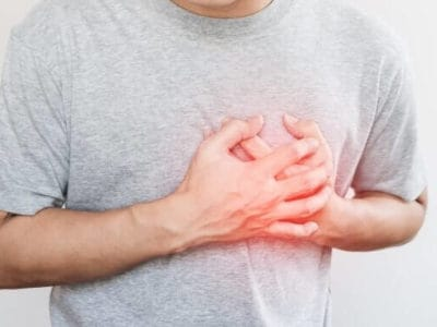 a man touching his heart, with red highlight of heart attack, and others heart disease concept, on white background