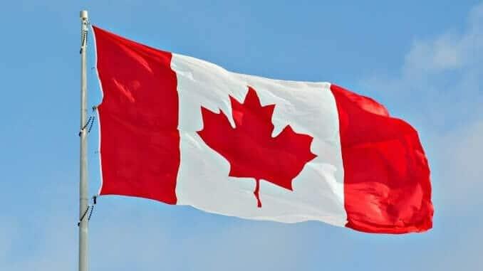 Flag of Canada flying against a blue sky.