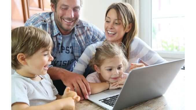 Familie mit Kindern sitzt vor Computer