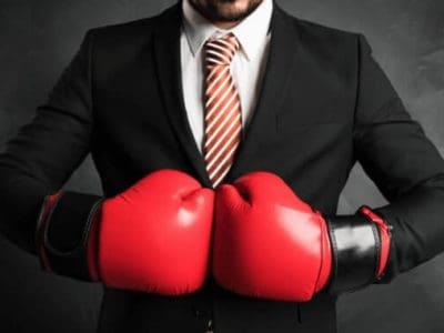Mann im Anzug mit Boxhandschuhen – der Kampf um die Produktbezeichnun Fleisch für Fleischalternativen