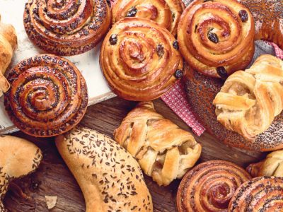 StockBreads, buns, croissants. Bakery ingredients on wooden background. Breakfast food concept. Top view