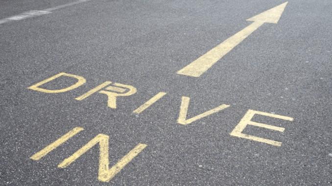 """Asphalt-Straße mit dem Schriftzug """"Drive-In"""" und einem Pfeil"""