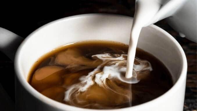 veganer Kaffeeweißer, der in eine Tasse Kaffee gegossen wird