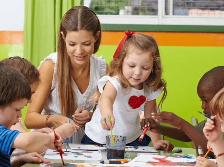 Kinder & Erzieherin malen im veganen Kindergarten