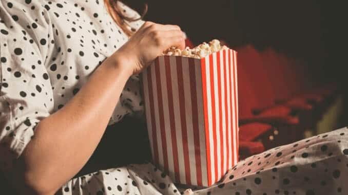 Frau mit Kleid sitzt im Kino und isst veganes Popcorn