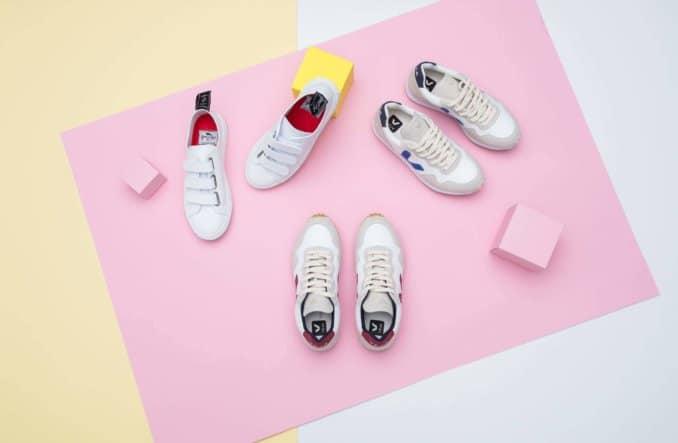 drei paar weiße Sneaker auf rosafarbenem Untergrund