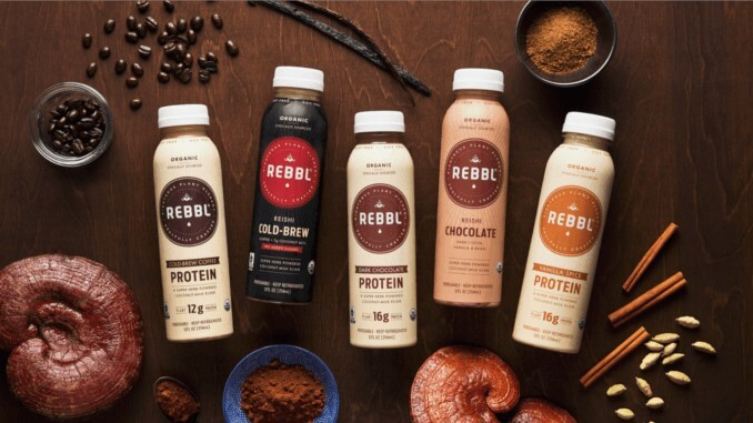 REBBL adaptogene vegane Getränke auf braunem Tisch umringt von Zutaten